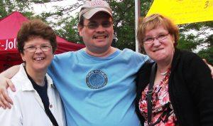 Jumelage. Photo portrait prise à l'extérieur, en été, d'un homme et de deux femmes. Les trois sourient et semblent heureux.
